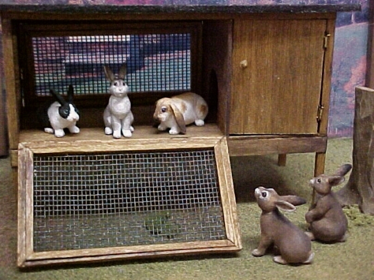 hand carved wood miniature bunnies with hand made hutch.