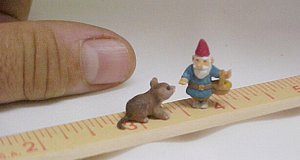 hand carved wood gnome feeding a mouse.