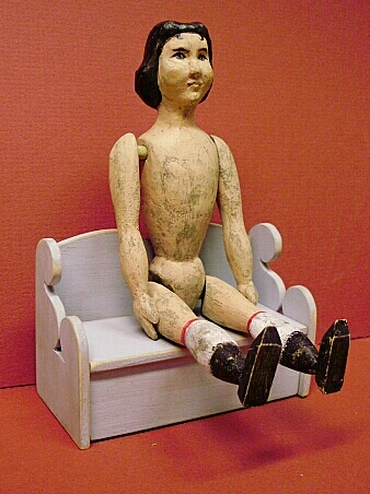 Hsnd carved Hitty Doll on her bench